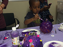 Kids painting pumpkins purple for epilepsy awareness